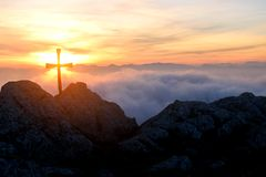 Backlit cross over the clouds Stock Photo