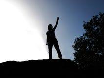 Backlit della persona alzando il braccio Fotografia Stock Libera da Diritti