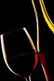 Backlit detail of a glass of red wine and the wine bottle Stock Images