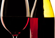 Backlit detail of a glass wine and the wine bottle against a sol Stock Images