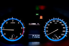 Backlit gauges of an automobile. Blue glowing meters with a whit Royalty Free Stock Photography