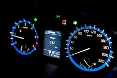 Backlit gauges of an automobile. Blue glowing meters with a whit Stock Photos
