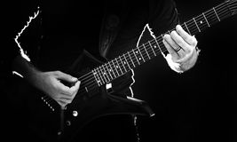 Backlit Guitar Player. Backlit Photo of a guitar player in all black playing rock music Royalty Free Stock Photo