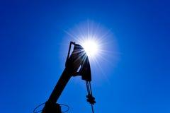 Backlit Head stålar för olje- pump för motvikt Olje- utrustning mot himlen och solen fotografering för bildbyråer
