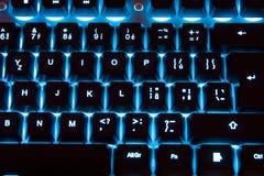 Backlit keyboard. Glows blue at night, modern gaming keyboard stock photo