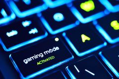 Gaming laptop. Backlit keyboard of laptop, focus on button, gaming mode activated Royalty Free Stock Images