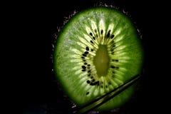 Backlit Kiwi. Kiwi fruit backlit on a fork stock photography