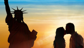 Backlit loving couple honeymoon in New York. With liberty statue and sunset background Royalty Free Stock Images