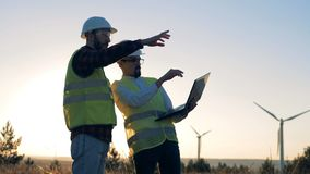 Backlit male energetics workers are having a discussion beside windmills. 4K stock video footage