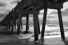 Backlit Pensacola Beach Fishing Pier (B&W). Black and white image of heavy surf crashing against the Pensacola Beach fishing pier on Santa Rosa Island, Florida Royalty Free Stock Image