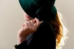 Backlit redhead hiding face behind green hat Royalty Free Stock Photos