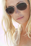 Backlit Blond Girl In Aviator Sunglasses. Backlit photograph of a stunningly beautiful and young blond woman in aviator sunglasses royalty free stock images