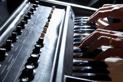 Backlit shallow focus shot of man& x27;s hands playing an old 1970s s. Ynth keyboard Royalty Free Illustration
