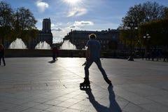 Backlit silhouet van een jonge mens het praktizeren rol die in het centrum van Parijs schaatst stock foto's