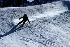 Backlit silhouette of man in action practicing ski going fast and aggressive down snow slope winter sport Royalty Free Stock Photo