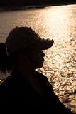 Backlit silhouette of a woman wearing a hat. Stock Photos