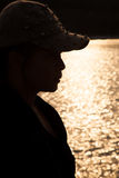 Backlit silhouette of a woman wearing a hat. Stock Images