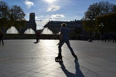 Backlit silhouette of a young man practising roller skating in the centre of Paris. stock photos