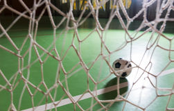 Backlit soccer ball in a goalpost. Atmospheric image of a backlit soccer ball in a goalpost in a darkened indoor court viewed through the net on the goal Stock Photo