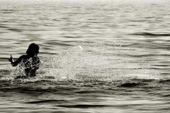 Backlit splash. Woman splashing water, sepia toned stock photo
