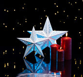 Backlit stars in blue with red candles Royalty Free Stock Photo