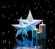 Backlit stars in blue with silver candles Royalty Free Stock Images