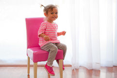 Backlit toddler girl on pink chair. Cute little baby girl wears a pink and gray outfit and sits on a bright pink chair. She is multicultural, asian and caucasion royalty free stock photo