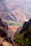 Backlit view down Waimea Canyon. Waimea Canyon in Kauai, Hawaii with the early morning sun shining up the valley behind the rocks stock image