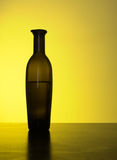 Backlit vintage olive oil bottle on counter. Stock Photo