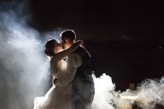 Bride and Groom kissing in fog at night Royalty Free Stock Photo