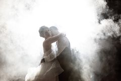 Bride and Groom kissing in fog at night royalty free stock image
