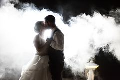 Bride and Groom kissing in fog at night Stock Image