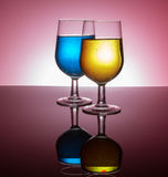 Backlit wine glasses. With colorful liquid on reflective surface stock photography