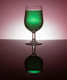 Backlit wine glasses. With colorful liquid on reflective surface stock photo