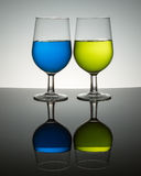 Backlit wine glasses. With colorful liquid on reflective surface royalty free stock photos