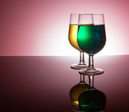 Backlit wine glasses. With colorful liquid on reflective surface royalty free stock photo