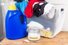 Backnatron mit Reinigungsmittel und Stapel der Schmutzwäsche stockfotografie
