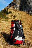 Backpack. Red backpack  on yellow grass with mountains on the background Stock Photography
