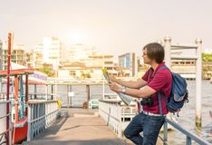 Backpack asian young man as a tourist looking at the map travell royalty free stock photography