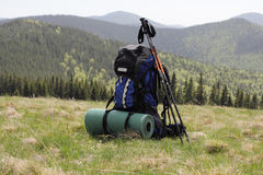 Backpack on the background of the snow-capped mountains with sticks for tracking Stock Photos