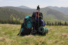 Backpack on the background of the snow-capped mountains with sticks for tracking Royalty Free Stock Image