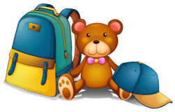 A backpack, a bear and a baseball cap Stock Photo