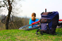 Backpack, bicycle and girl on nature Royalty Free Stock Images