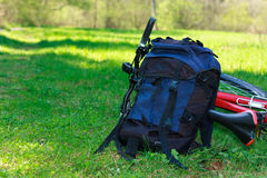 Backpack and Bike Lying on Green Grass Royalty Free Stock Image