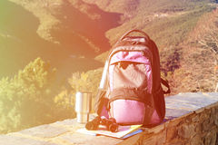 Backpack, binoculars, map in mountains, travel. Backpack, binoculars and map in mountains, travel concept Stock Photos