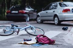 Child hit by a car. Backpack and broken child`s bike on the street. Child hit by a car concept Stock Photo