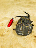 Backpack and canteen water bottle in the sand of a beach. Stock Image