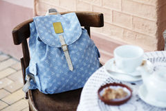 Backpack on the chair of cafe. Backpack forgotten on the chair cafe with coffee cups Royalty Free Stock Photography