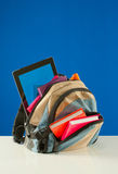 Backpack with colorful books and pablet PC. Backpack with colorful books and tablet PC on the blue background Stock Image