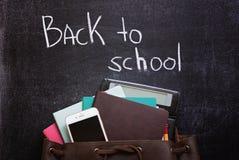 Backpack con la cancelleria ed il telefono cellulare della scuola sul fondo dell'ardesia Di nuovo al testo di banco Vista superio fotografia stock